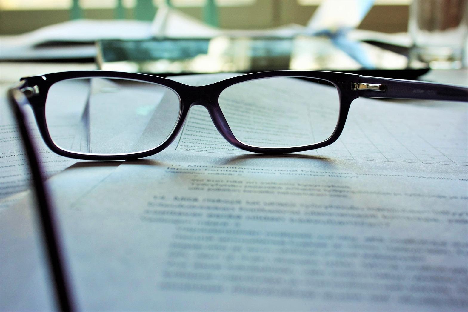 Okulary korekcyjne położone na kartkach papieru