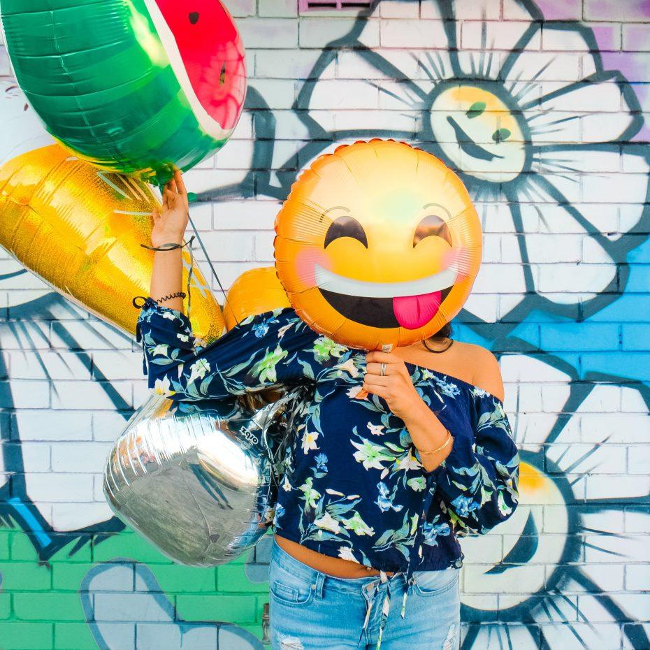 Kobieta zasłaniająca twarz balonem z uśmiechniętą emotikonką